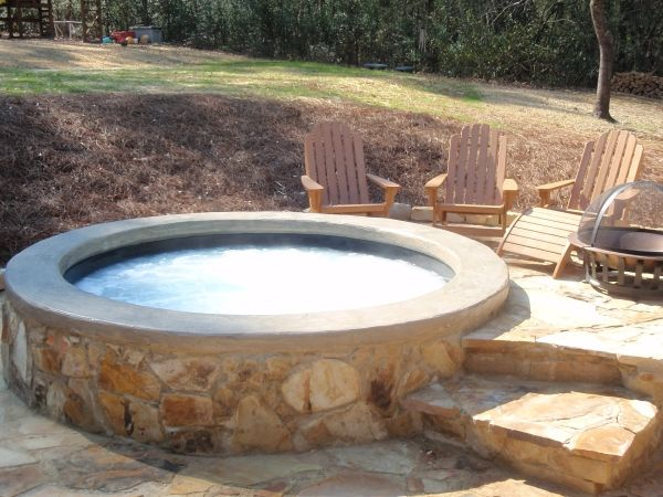 whirlpool im garten holzstühle steine rund