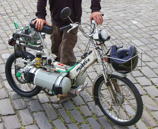 The TV presenter Jem Stansfield modified this small moped to function on compressed air stored in two high pressure carbon fiber tanks, like the ones that the firefighters use. The engine has been replaced by two rotary air engines. The two tanks can be fully charged in a matter of seconds from any air compressor. This compressed air bike can go about 8 miles, reach a speed of 18mph (about 30km/h).