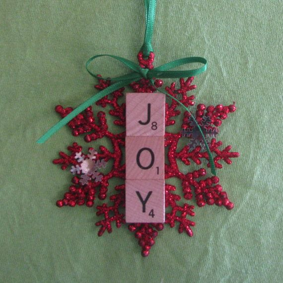 This is a 4 inch red glitter snowflake with the word JOY added using scrabble tiles. It is finished with a green bow and green ribbon for hanging.