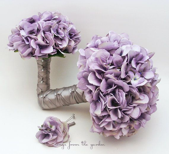 Beautiful silk hydrangea blooms in the perfect shade of antique lavender make an elegant and romantic bridal bouquet. I can create it for you as shown or customize it to fit your color scheme. We can work together to create a custom silk flower wedding package for your entire wedding party!    This 3-piece wedding flower package includes a custom silk flower bridal bouquet that is 9 in diameter and includes lavender silk hydrangea. The edge of the bouquet is finished with a collar of silver…