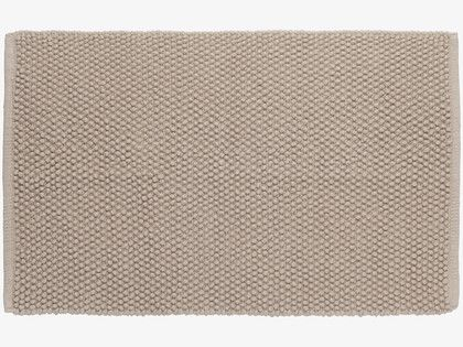 The step in the bathroom means that the floor space is too small for most bath mats. This one fits...  BOBBLE NEUTRAL Cotton Mushroom cream bath mat - HabitatUK