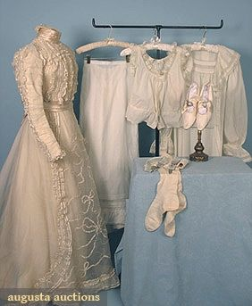 Wedding ensemble, American, c. 1900. Two-piece wedding dress of cream cotton organdy trimmed with ruched satin ribbon, petticoat and camisole set of fine white cotton trimmed with bobbin lace, white cotton nightgown, cream-colored kid leather shoes, white knit cotton stockings, and blue silk garters.
