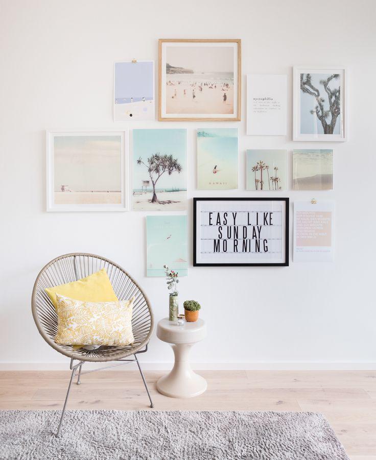 Ideen für eine Bilderwand im Schlafzimmer. Diese Wandcollage in der Salonhängung oder Petersburger Hängung vereint Palmen, Pastell, Urlaubsmotive und Typo zum Thema Schlaf