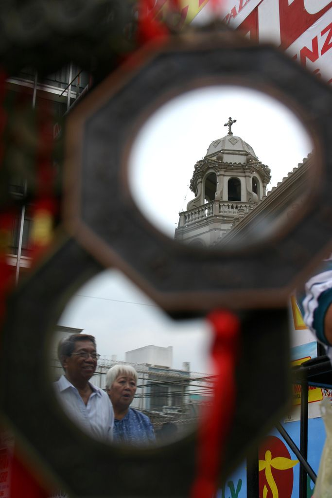 eclectic Quiapo | a Chinese feng-shui mirror peddled in Manila reflects the Quiapo Parish Church and a couple attending the 400 years of the Festivity in Quiapo.  thousands of devotees flock to Quiapo today to keep vigil before the image of the Black Nazarene of the Quiapo parish.  Quiapo, Manila Philippines