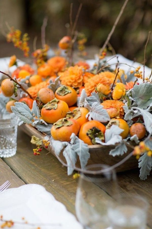 Persimmons Wedding Centerpiece: If you're not an apple fan, persimmons are another seasonal fruit that will look so elegant on your reception tables with their bright color and shiny skin. It's pretty how these are set against pale green-gray dusty miller so that they really pop.| 10 Festive Fall Fruit Wedding Decorations Ideas