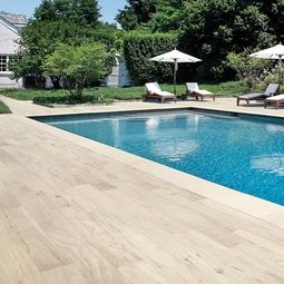 Wood plank porcelain tile makes for an easy to maintain for Pool surround ideas