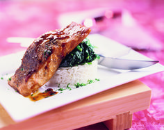 Zet de vispakketjes 15 minuten op een bakplaat midden in de oven. Verhit intussen de olie in een wok of hapjespan. Roerbak de spinazie en laat deze in 5 minuten slinken. Breng de spinazie op smaak met de gembersiroop, zout en versgemalen peper. Serveer de zalmpakketjes met de spinazie bij pandanrijst, notenrijst of gele rijst.