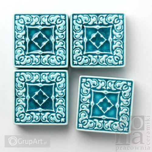 Cztery małe dekory ceramiczne z pięknym ornamentem. Wykonane z jasnej gliny. Szkliwione błyszczącym, efektowym, turkusowym szkliwem. Odporne na ścieranie, wysokie i niskie temperatury. Można wkleić je między innymi kaflami na ścianie lub po prostu zawiesić w dowolnym miejscu (każdy dekor posiada z tyłu rowek, umożliwiający zawieszenie). Inne dekory dostępne na: http://www.grupart.pl/tag/dekory