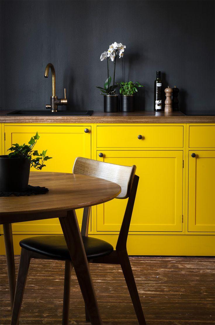 Keittiössä yhdistyy kirkkaan keltainen, tumman harmaa, lämmin puu sekä pienet messinkiset yksityiskohdat