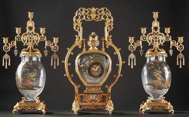 """Garniture de chemine japonisante signée par L'Escalier de Cristal, Paris, vers  1875  Bronze ciselé, ajouré, patiné et doré « vieux ton or », cristal de verre dit """"martelé"""" émaillé.   Comprenant une pendule et une paire de candélabres en bronze finement ciselé, doré façon « vieux ton or » et cristal de verre dit « martelé » émaillé."""