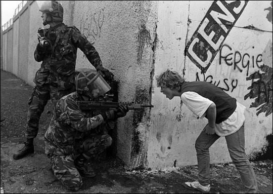 An Irish teenager yells at British soldiers during unrest in Northern Ireland