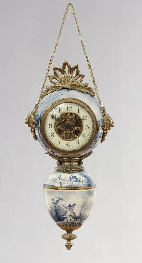 Unusual French Hanging Clock by Japy Freres, fourth quarter 19th century, comprised of Delft-style porcelain and gilt metal, the lower acorn-shaped portion decorated with windmills in a country scene, and with a lower finial of laurel leaves and a pine cone, the fluted gilt-metal throat mounted with a laurel wreath, which attaches the lower section to the porcelain sphere, decorated to match the base, holding the clock, set with a cream-colored porcelain chapter ring  bezel