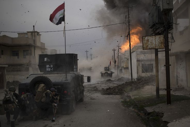 Spot News, Third Prize, Singles—<i>Battle For Mosul</i>: A car bomb explodes next to Iraqi special forces armored vehicles as they advance towards Islamic State-held territory in Mosul, Iraq, on November 16, 2016. The Iraqi Special Operations Forces, also known as the Golden Division, is the Iraqi unit that leads the fight against the Islamic State with the support of the airstrikes of the Coalition Forces. They were the first forces to enter the Islamic State-held city of Mosul in November…