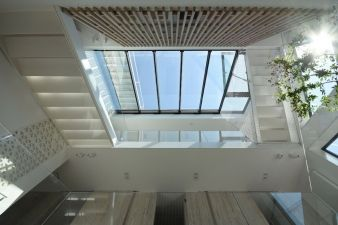 The living spaces are organized around a central void that extends to the top of the structure