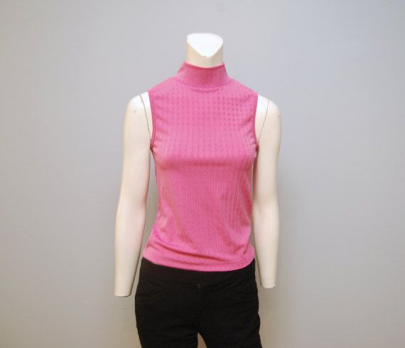 Adorable sleeveless top from the 1990s or 1980s. Fabric is a polyester, nylon and lycra blend. Slinky textured fabric (texture can been seen in the close up photos). Size is large, but fits small in my opinion, so please see measurements below. Keep in mind that the fabric is stretchy. In excellent vintage condition with no visible imperfections!  Measurements (taken when laid flat): Armpit-Armpit: 15 Waist: 14 Length: 20