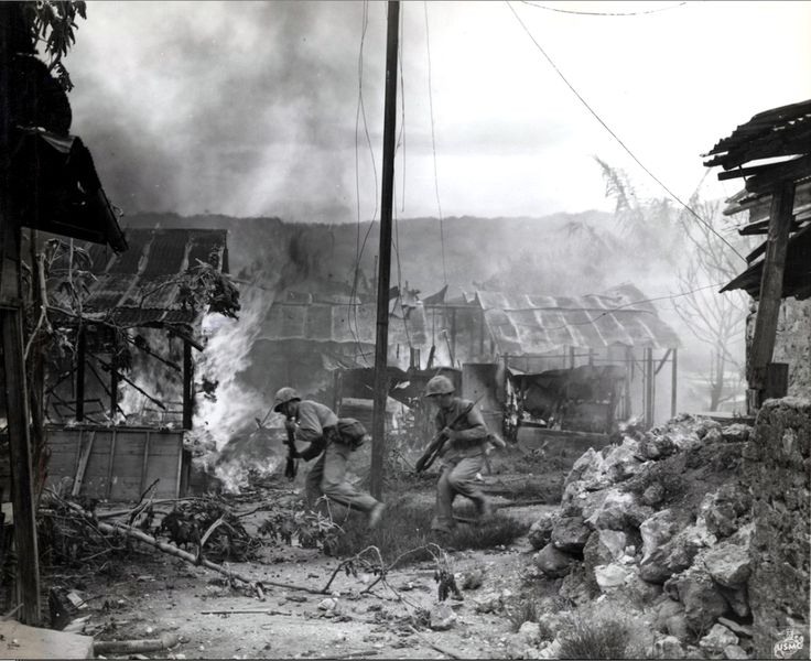 U.S. Marine infantrymen move quickly to take up new positions against Japanese troops during the Battle of Saipan, while the village of Garapan burns. Garapan, Saipan, Northern Mariana Islands. 3 July 1944