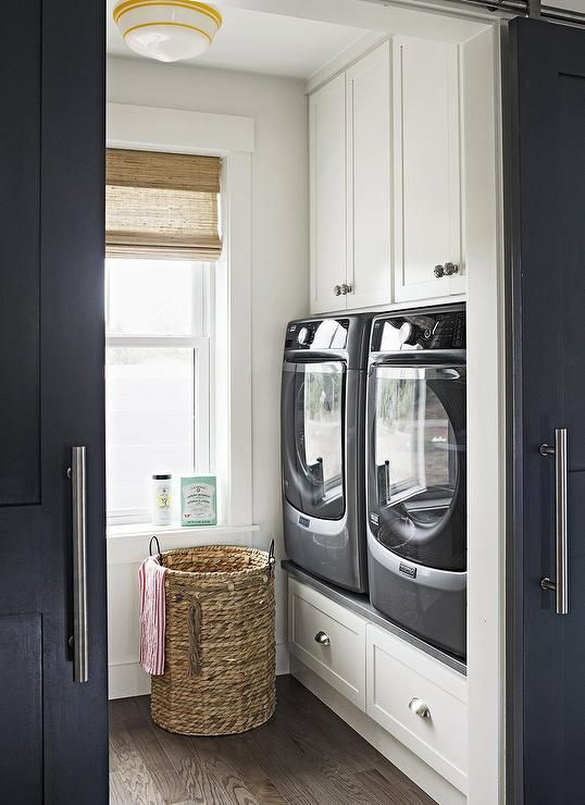 Two white shaker cabinets adorned with gray knobs hover over gray maytag front-load washer and dryer placed atop a built-in riser fitted with drawers adorned with cup pulls.