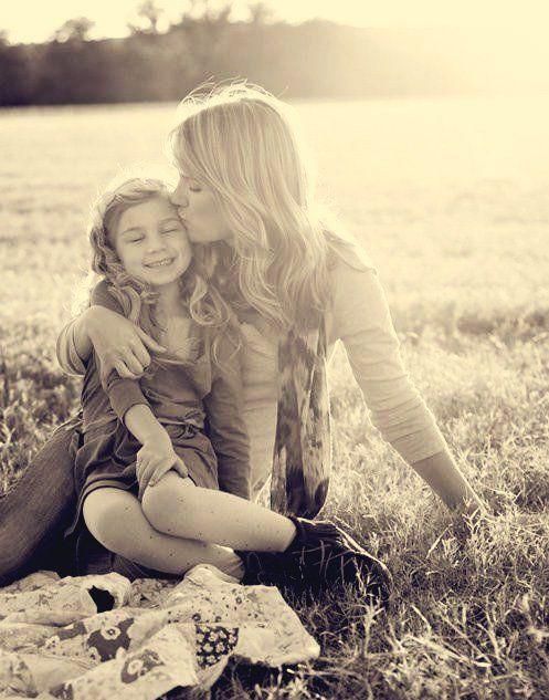 mamá con su hija sentadas en el pasto