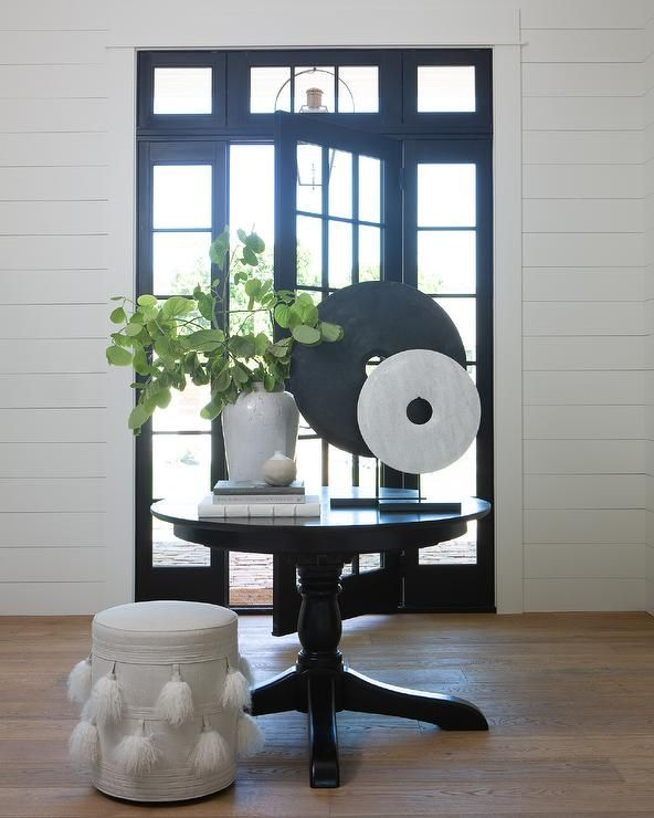 A White Tassel Stool Sits At A Well Styled Round Black Foyer Table Placed In The Middle Of A Foyer Entryway Round Table Foyer Table Round Table Decor