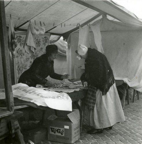 Handel. Markt. Een vrouw in klederdracht bekijkt een kraampje waar o.a. tafelkleden en zemen lappen verkocht worden. De koopvrouw met bondmuts geeft uitleg over een zemen lap. Goes, Nederland. Datum onbekend.
