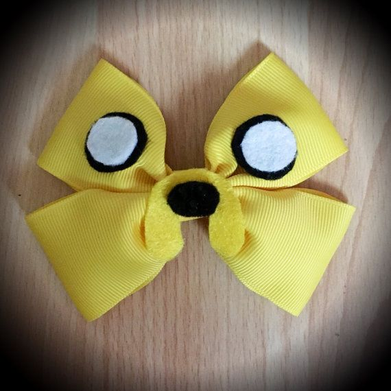 Adventure Time Jake the Dog Character Inspired Yellow Hair Bow.  Yellow Grosgrain Ribbon Decorated with Black and White Felt Details and Black Rhinestones.  Mounted on an alligator clip.  I can do custom bows, just let me know if youd like something specific.  Price is for single bow.