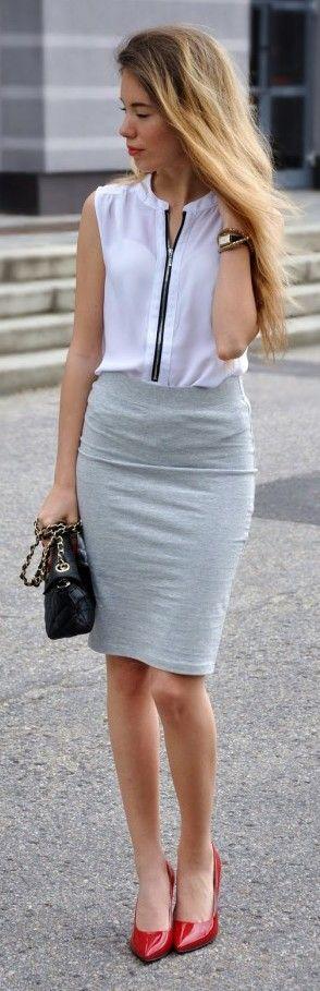 Linda blusa con cuello alto, cierre al frente con falda tubo gris tacones rojos y cartea negra