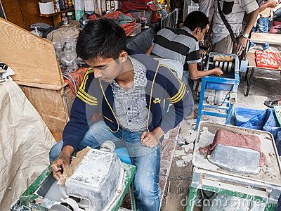 Batam, Indonesia. February 7th, 2015. An Indonesian man smoth a gemstone in a market.