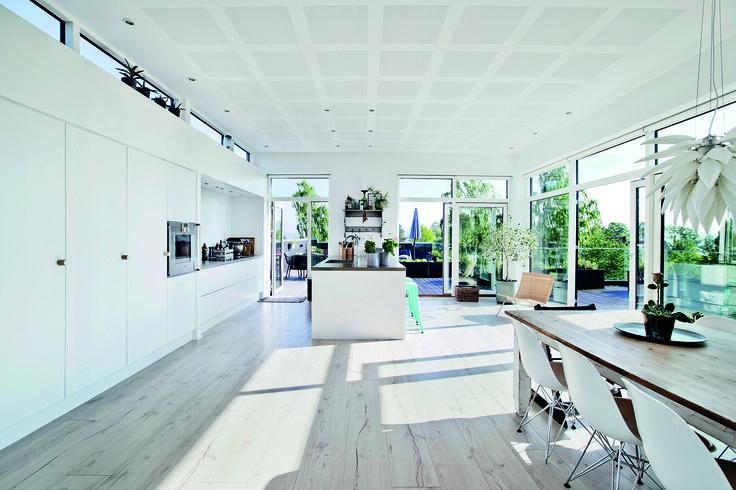 Tre store døre kan skydes til side, så køkken-alrum og tagterrasse i sommermånederne flyder sammen til ét stort rum. Se boligen på www.jke-design.dk