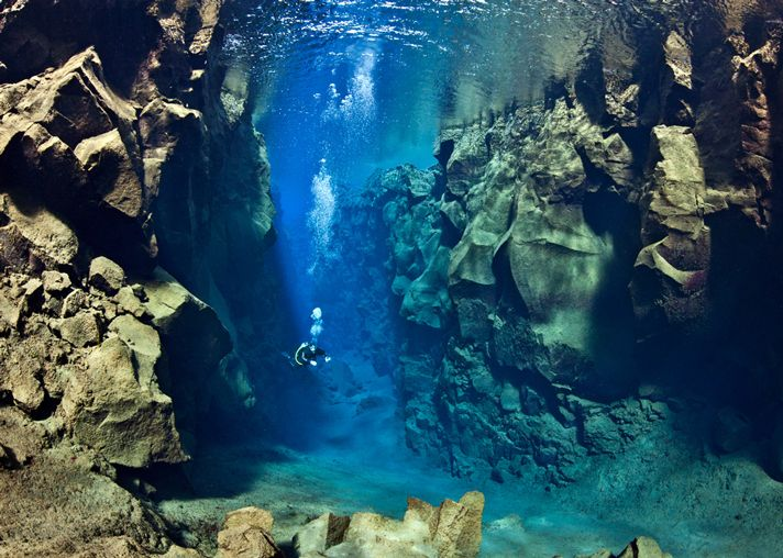 Divers and snorkelers swim between the North American and Eurasian continental plates in some of the clearest water on Earth with over 100 meters of water visibility.