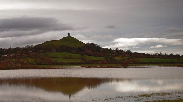 """Glastonbury Tor, Somerset. Tor (meaning """"hill""""). The spot seems to have been called Ynys yr Afalon (meaning """"The Isle of Avalon"""") by the Britons, and it is believed by some to be the Avalon of Arthurian legend. The Celtic name of the Tor was Ynys Wydryn, or Ynys Gutrin, meaning """"Isle of Glass"""". At this time the plain was flooded, the isle becoming a peninsula at low tide. Excavations on Glastonbury Tor revealed evidence of Roman occupation and remains of a 5th century fort."""