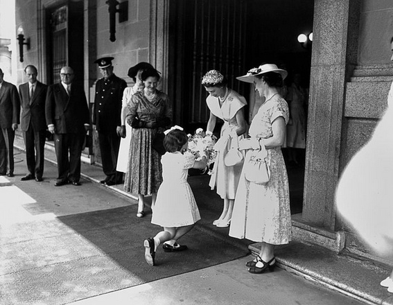 "In this photograph, a young girl curtsies before Queen Elizabeth II and offers her a bouquet of flowers. Just beyond them is the entry to Brisbane City Hall, where on 10 March 1954 excited locals were invited to meet the royal couple at ""The Royal Ball"".   The event included a temporary rainforest, complete with Queensland flora & fauna, a waterfall and koalas from Lone Pine. #hereisourstory http://www.museumofbrisbane.com.au/here-is-our-story/ (Image courtesy State Library of Queensland)"