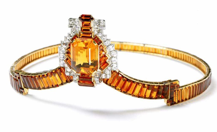 In 1937 Cartier's London house created 27 tiaras, including this citrine and diamond tiara, many of which were worn at the coronation of George VI. This tiara is typical of the era in the style of settings and use of coloured stones together with diamonds. The central element can be dismounted and worn as a brooch.