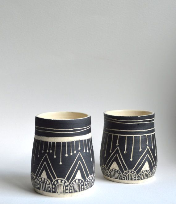 These tumblers are wheel thrown, painted with a black velvet underglaze, and include hand carved designs. Inside of tumblers are glazed with a matte clear