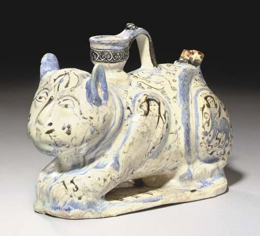 A MINA'I POTTERY CAT CENTRAL IRAN, CIRCA 1200 Crouching on flat base, the head with pricked ears, long nose and irregular eyes, the thick body with moulded legs, a vertical spout with loop handle rising from the neck, the rump with small double spout, the white ground decorated with natural features, human figures, harpies and arabesques within blue-outlined panels, the main spout with black arabesque band