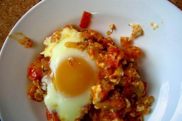 Μια τηγανιά με ντομάτα, κρεμμύδι και φέτα, μόλις ροδισμένα, απλωμένα σε πυρέξ και από πάνω 2-3 αυγά. Όλα αυτά στον φούρνο, να σφίξουν και να ψηθούν, και σε 20 λεπτά έχεις τούτο το θαύμα μοιρασμένο στα πιάτα.