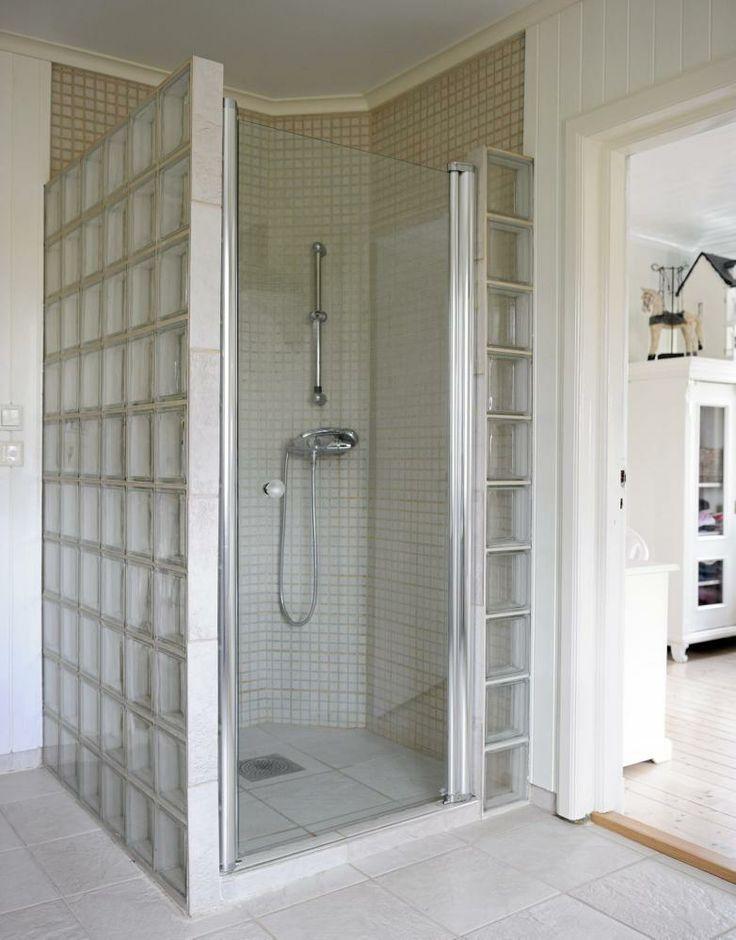 Dusjen er dekket av glassbyggersteiner og en glassdør. Små mosaikkfliser dekker veggene inne i dusjen.