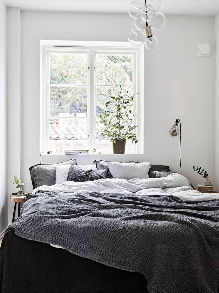 grey sheets, plant, modern bubble light pendent, white walls
