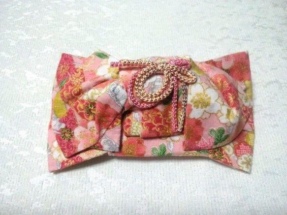着物帯結び;花文庫結びを型どったバレッタです。文庫結びをアレンジした花文庫結びです。可憐な結び方です。春らしい彩取りどり桜を中心に百花の描かれた柄で、桜の咲き乱れる春爛漫をイメージしました。ピンクの春色に赤が差し色となり、華やかさを演出します。和装時に着物帯の結び方と合わせてお使い頂くと、更にお洒落感が増します。普段の洋服に合わせて頂けば、日常に和の癒しを気軽に身に付けて頂けると思います。バレッタは10cmの大きめのCLIPFRANCEを使用しており、まとめ髪も可能です。『桜ハンドメイド2017』『春ハンドメイド2017』『ハンドメイド新作2017』十分気をつけておりますが、手作りのため、接着剤のはみ出しがあるものが稀に御座います。ご了承の上、ご注文頂きますようお願い申し上げます。