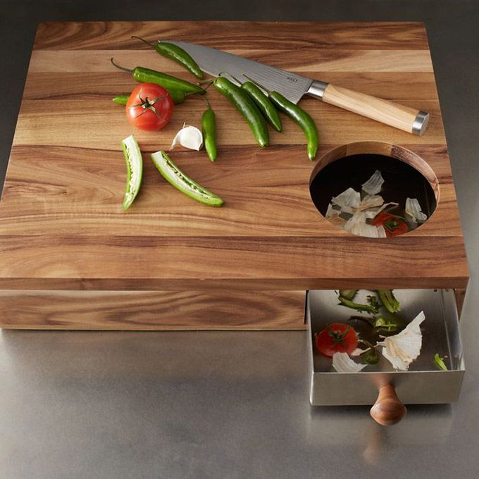 This cutting board has a hole in one corner that allows you to sweep peelings and trimmings into a hidden metal drawer that you can pull out to easily throw all discards. Good idea!
