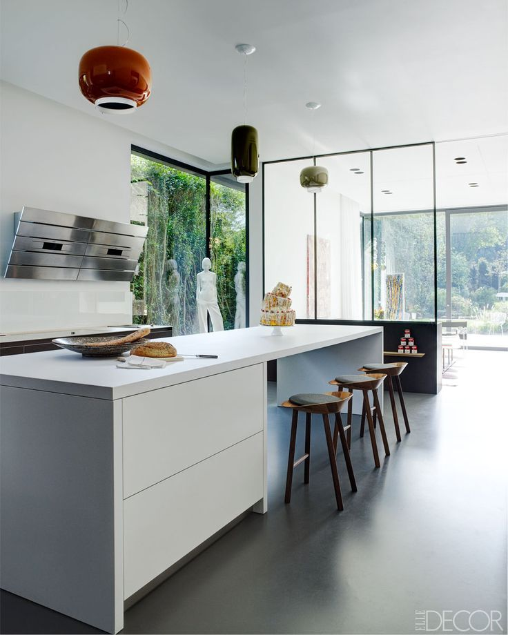 The kitchen island is by Bulthaup, the vent hood is by AEG, the stools are by E15, and the hanging light fixtures are by Ionna Vautrin.