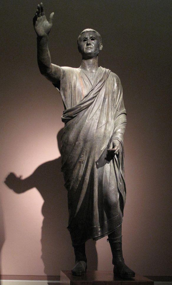 L'Arringatore, statua di Aulo Metello, I a.C., bronzo a tutto tondo, Museo Archeologico di Firenze. Il braccio è sollevato in un gesto democratico (quello di richiedere la parola) e contenuto, il panneggio della toga è sobrio; l'utilizzo del bronzo è indice di un'alta committenza.