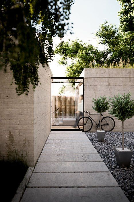 Clean and contemporary front entrance. Pots feel under scale but I love the broad stepper path and monolithic walls.
