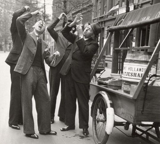 Customers eating herring in the traditional Dutch way, the Netherlands, Rotterdam, 1937.