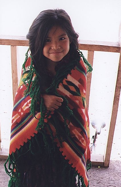 Stacey Blackrock in traditional Navajo clothes and a traditional Navajo Blanket.