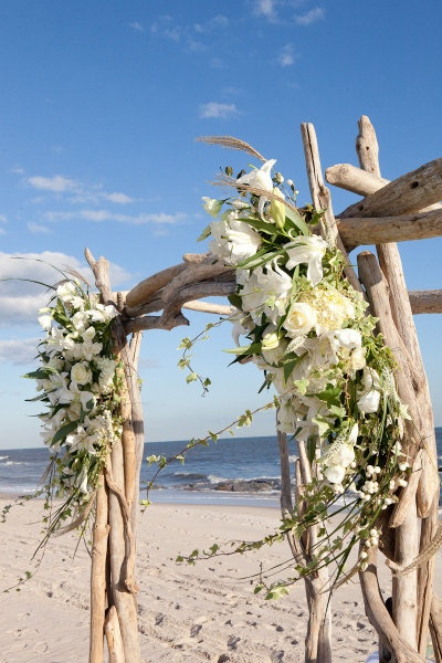This arrangement featuring white lilies brings ornamentation to a simplistic beach wedding.