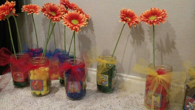 Curious George centerpieces: mason jars, pom poms, curious george matching game cards, fake flowers and netting for bows. Super easy!