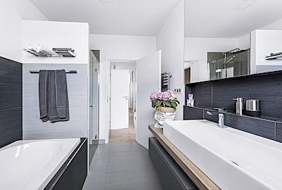 Minimalistická, barevně neutrální koupelna je nadčasová a její vzhled lze měnit libovolnými barevnými doplňky. Závěsné skříňky a deska z běleného povoskovaného dubu odpuzující vodu jsou vyrobené na míru.