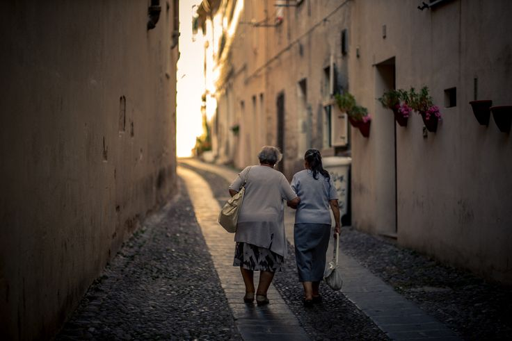 Friendship - Taken during our summer trip to Alghero, Italy. I noticed two old ladies, old friends walking in the old town. I took a picture of them, while they were going towards sunset in one of the narrow streets of Alghero. I think its been fantastic moment of two fantastic people.