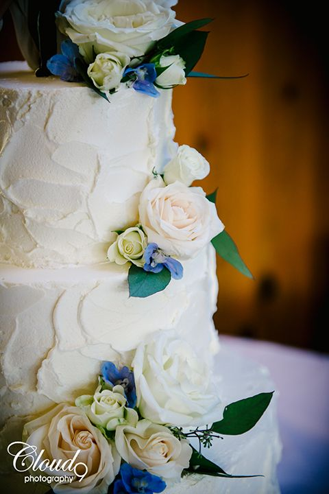 Rustic malibu wedding at calamigos ranch three tier white wedding cake with white and green flower decor on side with bride and groom figures on top on light blue table linen wedding photo idea