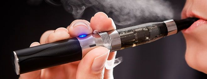 Close up of a woman inhaling from an electronic cigarette. NO